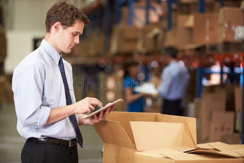 Менеджер в коробках склада проверяя используя таблетку цифров стоковое фото rf