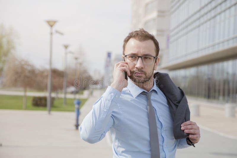 Менеджер говоря на умном телефоне outdoors стоковое изображение rf