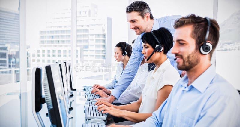 Менеджер и исполнительные власти с шлемофонами используя компьютеры стоковые фотографии rf