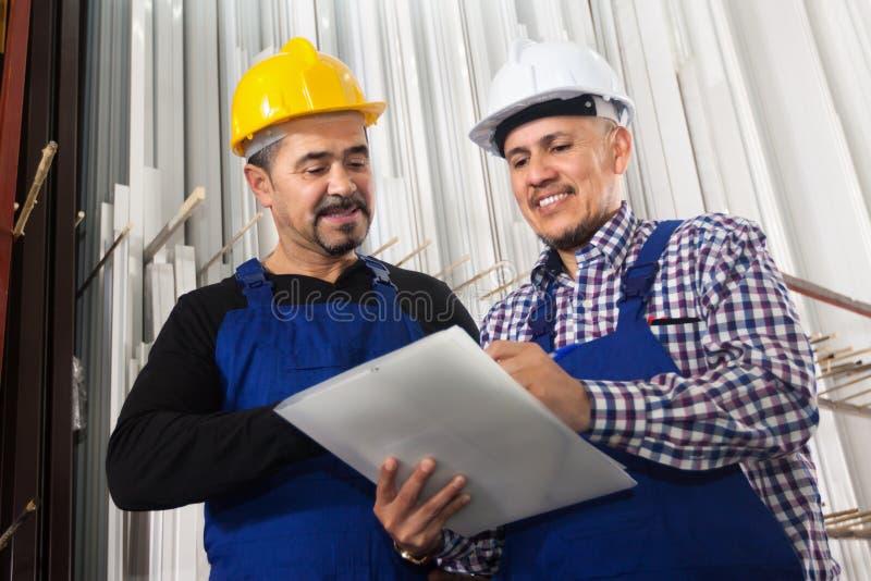 Менеджер обсуждая работу на фабрике окон PVC стоковые изображения