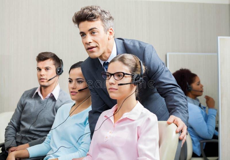 Менеджер объясняя к работнику в центре телефонного обслуживания стоковое фото
