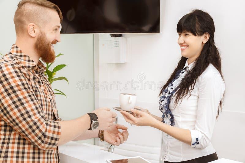 Менеджер офиса предлагая клиенту чашка чаю стоковая фотография rf