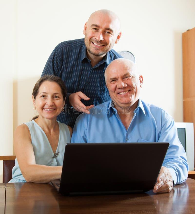Менеджер помогая к старшим парам с компьтер-книжкой стоковые фотографии rf