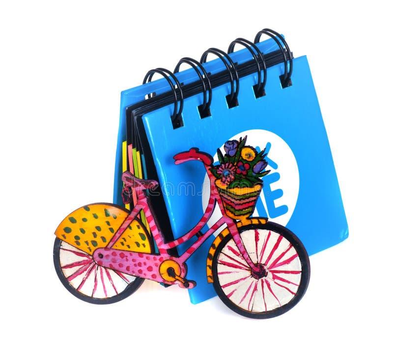 Меньшая голубая тетрадь рядом с которой малый велосипед стоковое изображение rf
