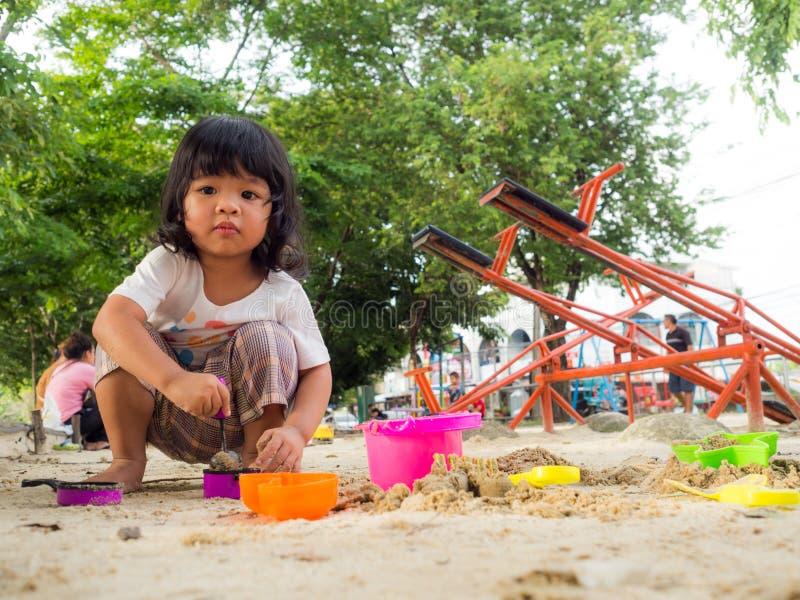 Меньшая девушка Азии сидя в ящике с песком и играя с ведром лопаткоулавливателя песка игрушки стоковое фото