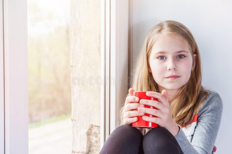 Меньшая девушка красоты с чашкой на окне стоковая фотография rf