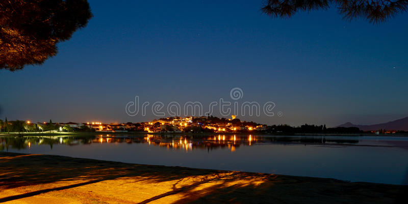 Меньшая деревня отражая в озере к ноча стоковые изображения rf
