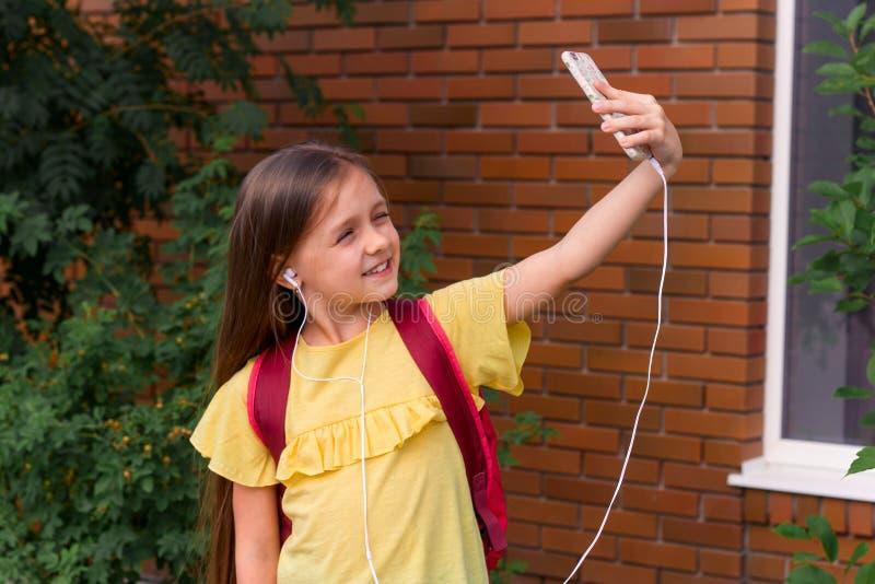 меньшая красивая девушка используя мобильный телефон и принимающ selfie стоковая фотография rf