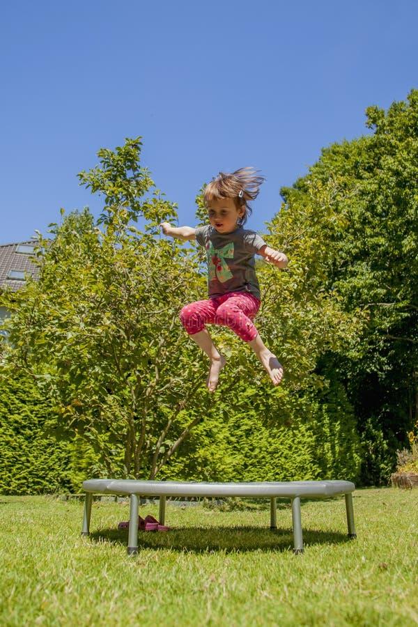 Меньшая очень счастливая милая девушка ребенка наслаждается поскакать на батут стоковые фото