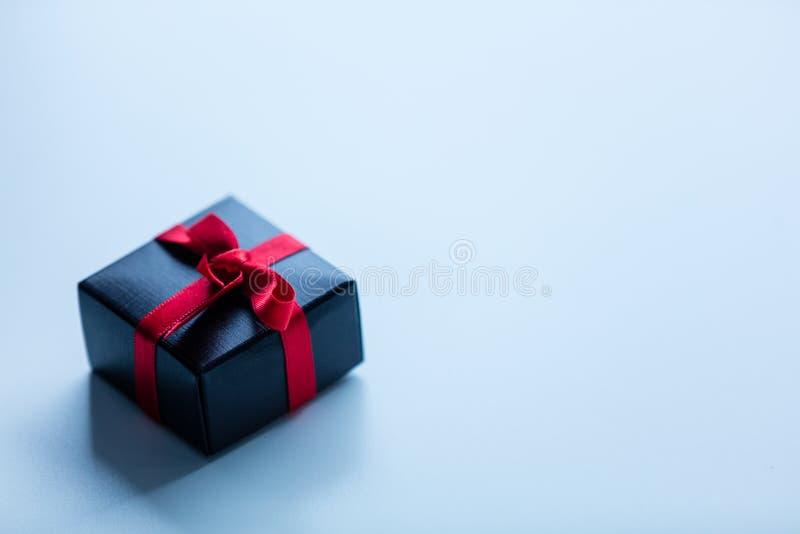 Меньшая подарочная коробка на белом стекле стоковое фото rf