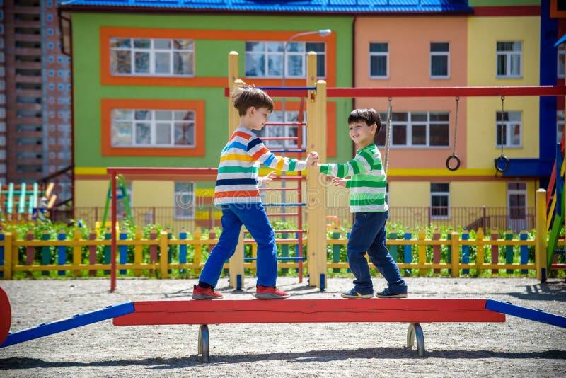 2 меньшие школа и preschool мальчики детей играя на спортивной площадке outdoors совместно дети имея конкуренцию стоя на журнале стоковые изображения rf