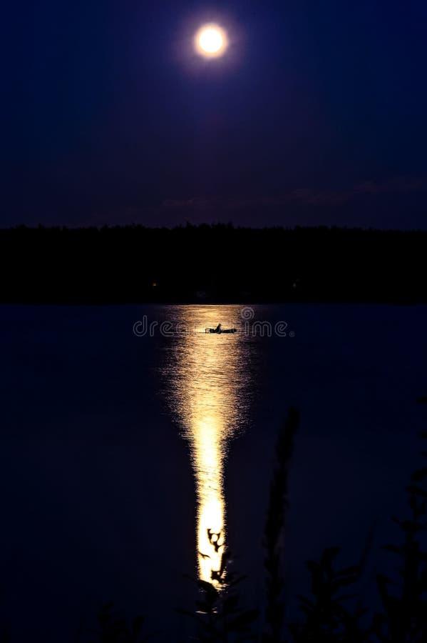 Меньший ботинок рыбной ловли на реке на ноче осветил полнолунием стоковая фотография