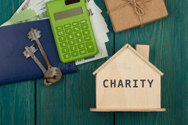 Меньший дом с текстом & x22; Charity& x22; , ключи, калькулятор, пасспорт, подарочная коробка, деньги стоковая фотография