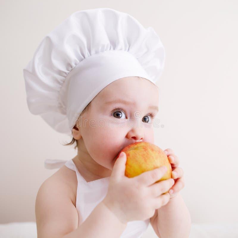 Меньший кашевар ест яблоко стоковая фотография rf