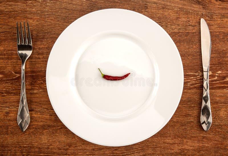 Меньший красный пеец на белой плите с kitchenware на tabl стоковые изображения