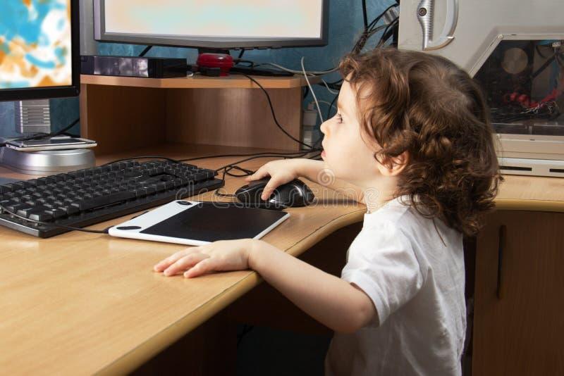 Меньший 3 - летний ребенок 2 в белых clothers рисует на домашнем компьютере в планшете чертежа графиков мониторы 2 E стоковые фото