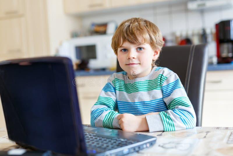 Меньший мальчик ребенк школы играя игру и занимаясь серфингом интернет на компьютере Ребенок имея потеху с учить на ПК Образовани стоковая фотография