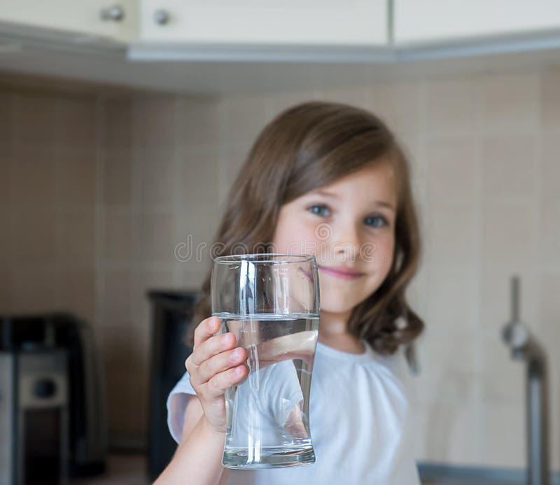 Меньший ребенок выпивает чистую воду дома, конец вверх Кавказская милая девушка с длинными волосами держит стекло воды в ее руке стоковые изображения rf