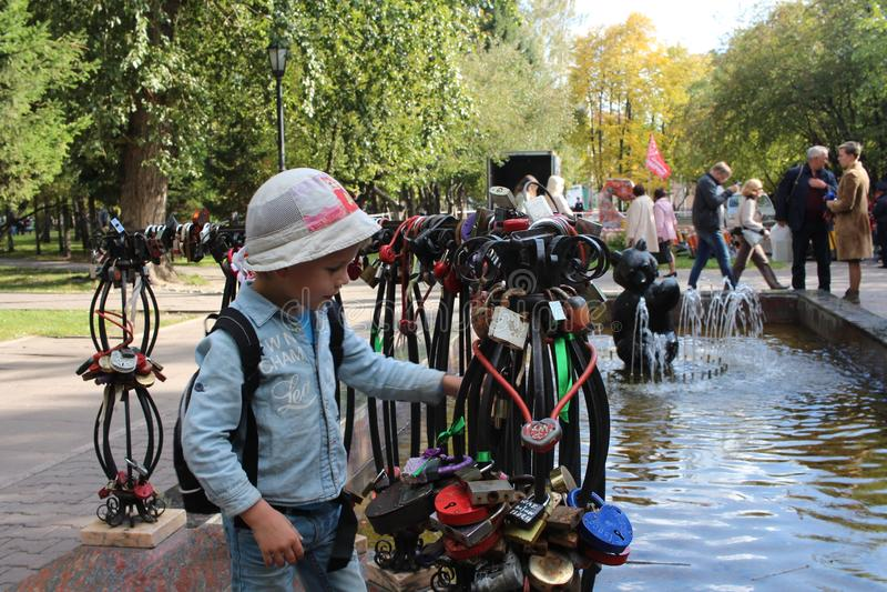 Меньший ребенок идя рассматривающ украшения на декоративных перилах фонтана в первом квадрате в Новосибирске стоковые изображения rf