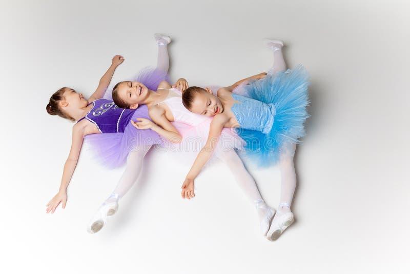 3 меньших девушки балета в балетной пачке лежа и представляя совместно стоковые фото