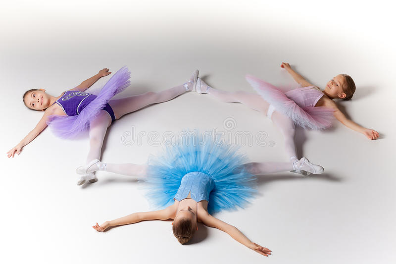 3 меньших девушки балета в балетной пачке лежа и представляя совместно стоковое изображение rf