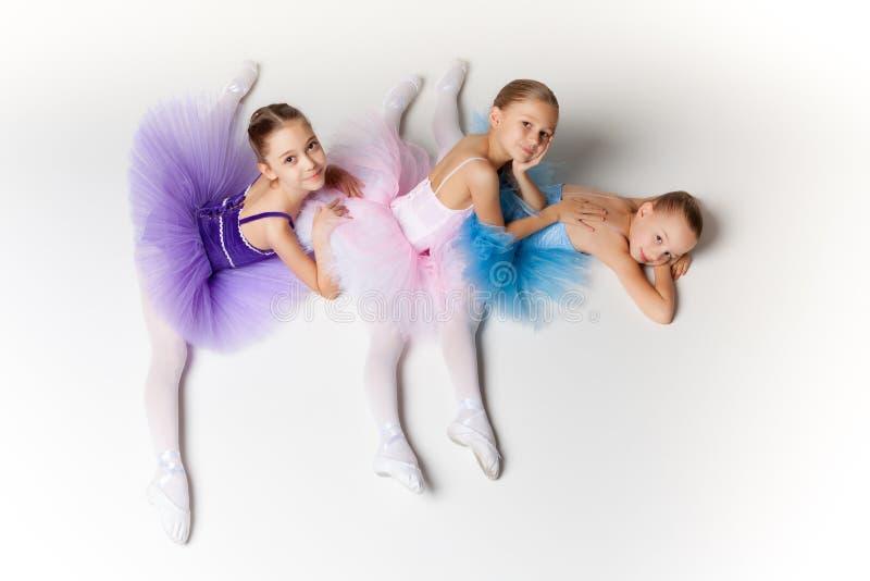 3 меньших девушки балета сидя в балетной пачке и представляя совместно стоковые изображения