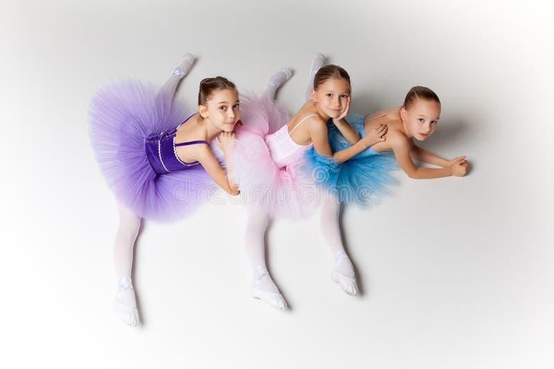 3 меньших девушки балета сидя в балетной пачке и представляя совместно стоковое фото rf