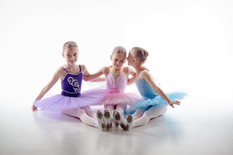 3 меньших девушки балета сидя в балетной пачке и представляя совместно стоковые фото