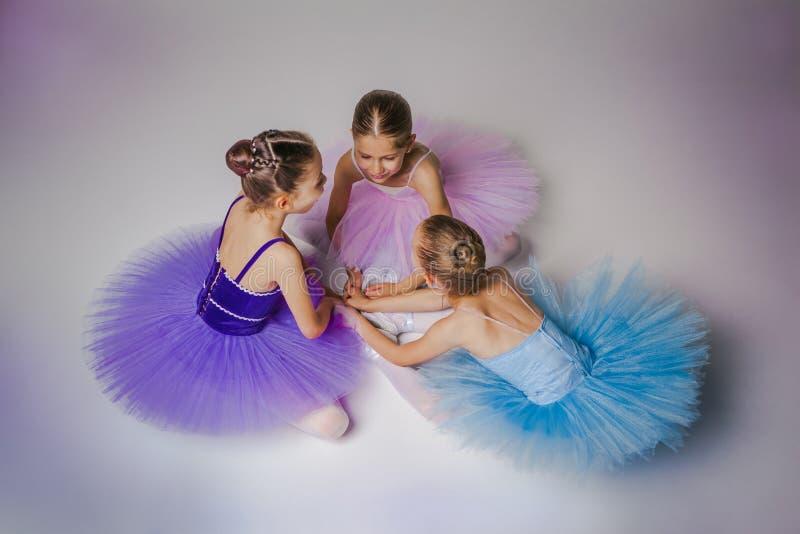 3 меньших девушки балета сидя в балетной пачке и стоковое фото rf