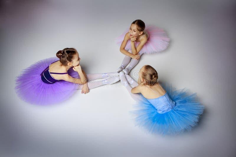 3 меньших девушки балета сидя в балетной пачке стоковое изображение