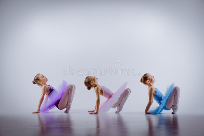 3 меньших девушки балета сидя в балетных пачках и стоковые изображения