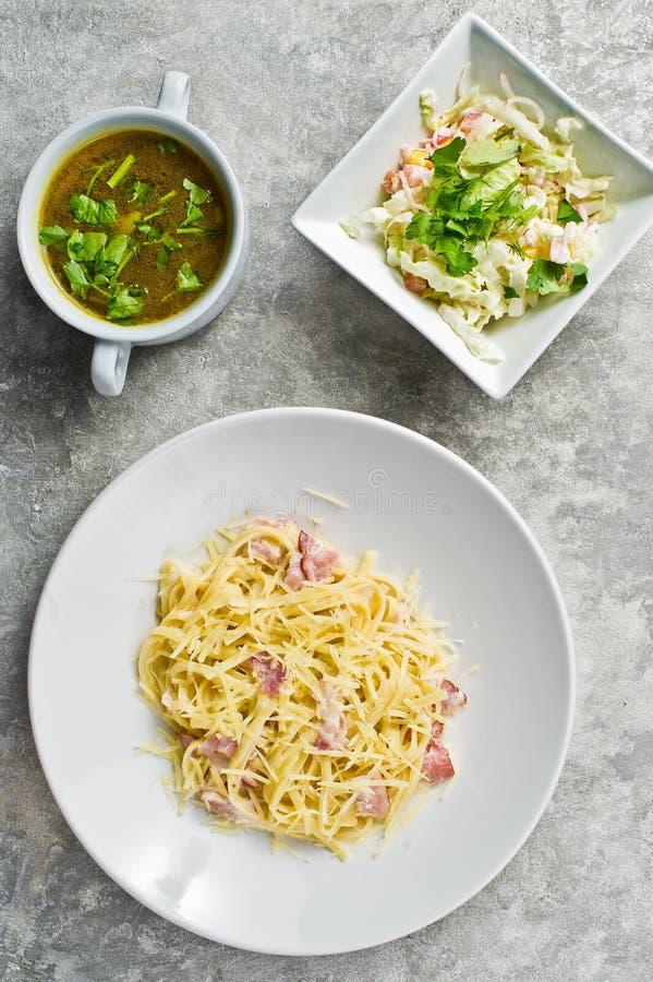 Меню бизнес-ланча, макаронные изделия Carbonara, зеленый салат и куриный суп стоковое изображение