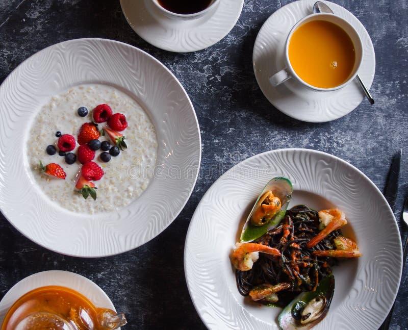 Меню на кафе, завтраке и обеде, каше с ягодами и макаронных изделиях с морепродуктами, булгуром и черными спагетти с креветками стоковые фотографии rf