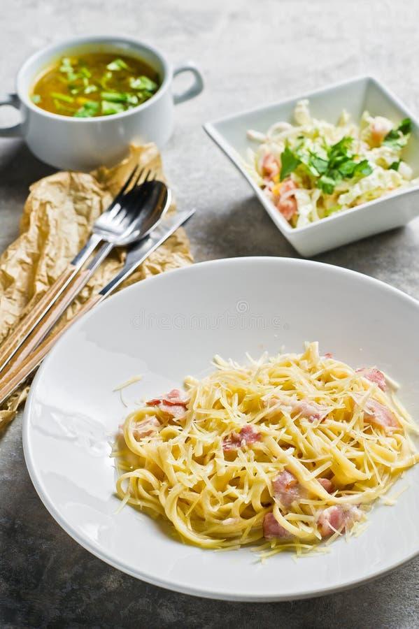Меню обеда ресторанного бизнеса, макаронные изделия Carbonara, зеленый салат и куриный суп стоковые изображения