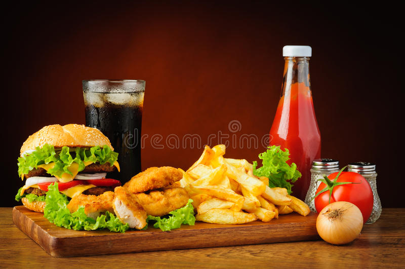 Меню фаст-фуда с гамбургером, наггетами цыпленка и фраями француза стоковое изображение rf
