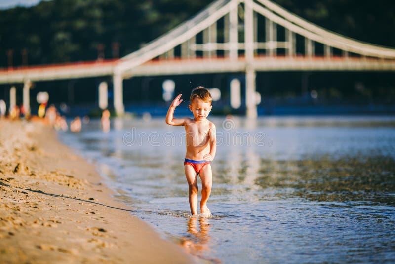 Мероприятия на свежем воздухе лета темы около реки на пляже города в Киеве Украине Немногое смешной ребенок бежать вдоль реки стоковое фото rf