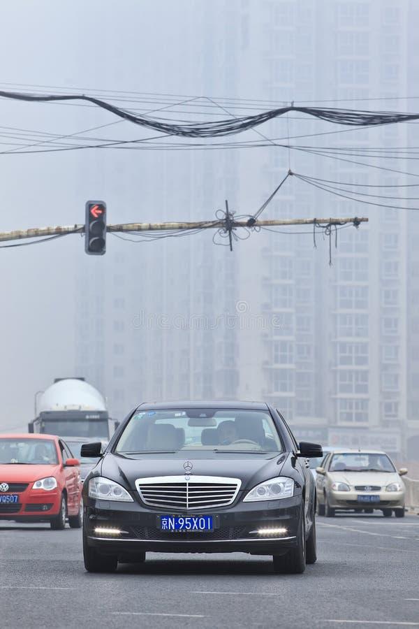 Мерседес-benz вытягивает вверх на пересечении покрытом с смогом, Пекином, Китаем стоковое фото