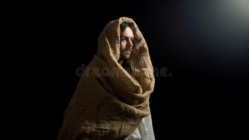 Мессия в робе стоя в темноте, вероисповедании как надежда для спасения в грешном мире стоковые фото