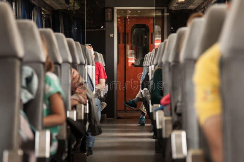 Места пассажирского автомобиля в европейском поезде при люди усаживая на его, с одиночным лобби в центре стоковое изображение rf