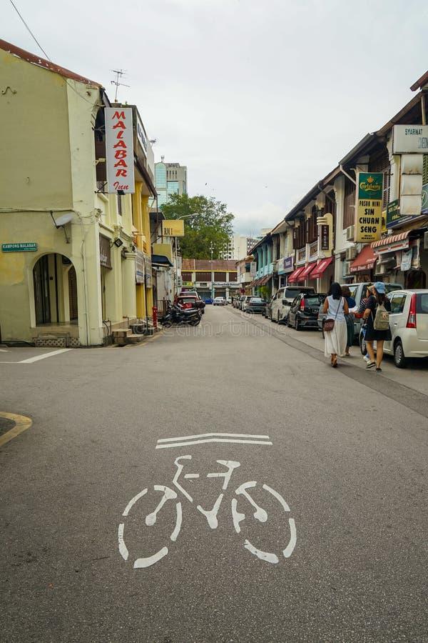 Местная дорога в знаке майны направления велосипеда показа городка Джордж на поверхности улицы с shophouse традиционного наследия стоковое фото rf