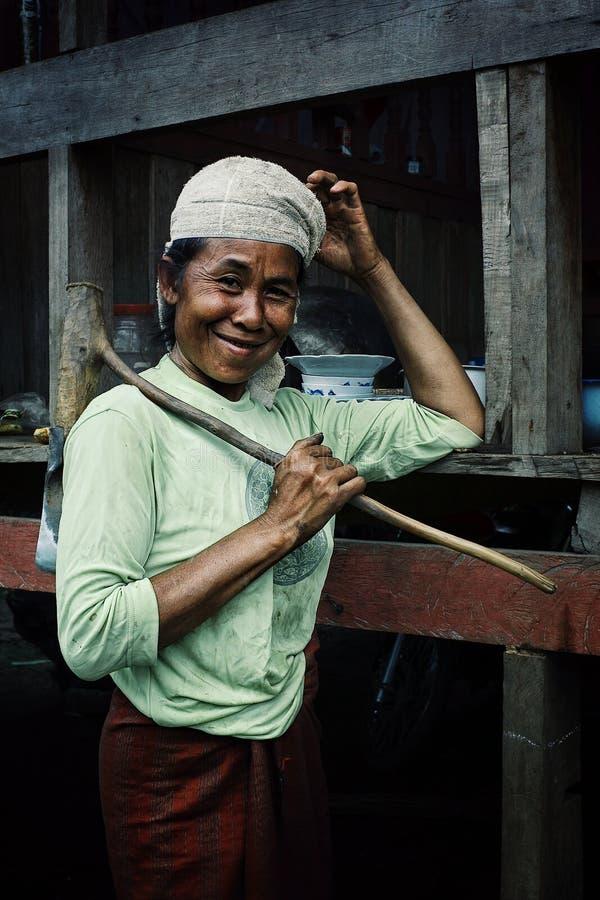 местная женщина деревни при большая традиционная ось ждать ее обед, который нужно подготовить стоковая фотография rf