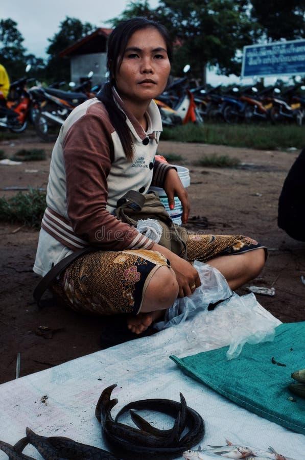 местная молодая женщина продавая рыб и угрей на рынке деревни стоковая фотография