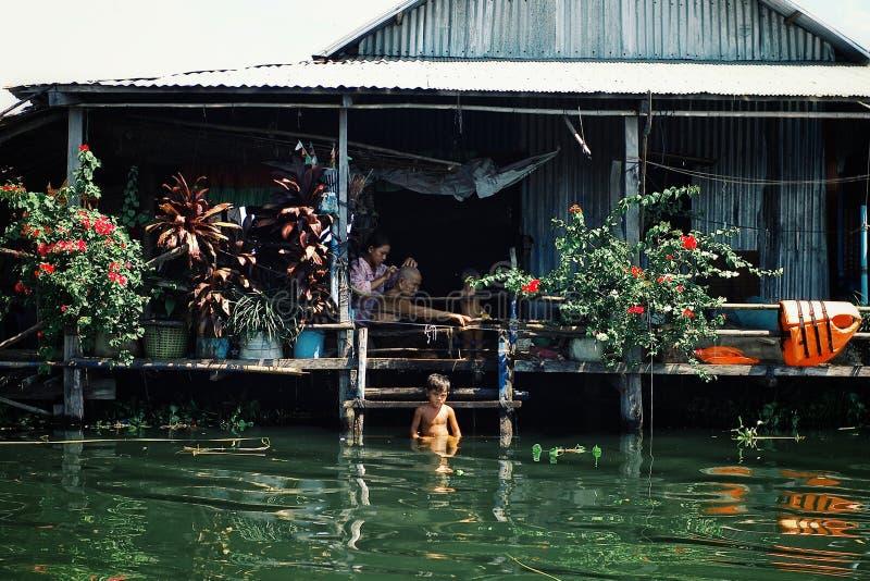 местная семья наслаждаясь тихим после полудня на их доме дома ходулей пока бреющ и имеющ ванну стоковое изображение