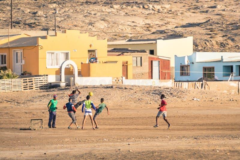 Местное молодые люди играя футбол футбола на спортивной площадке посёлка в Намибии стоковые изображения