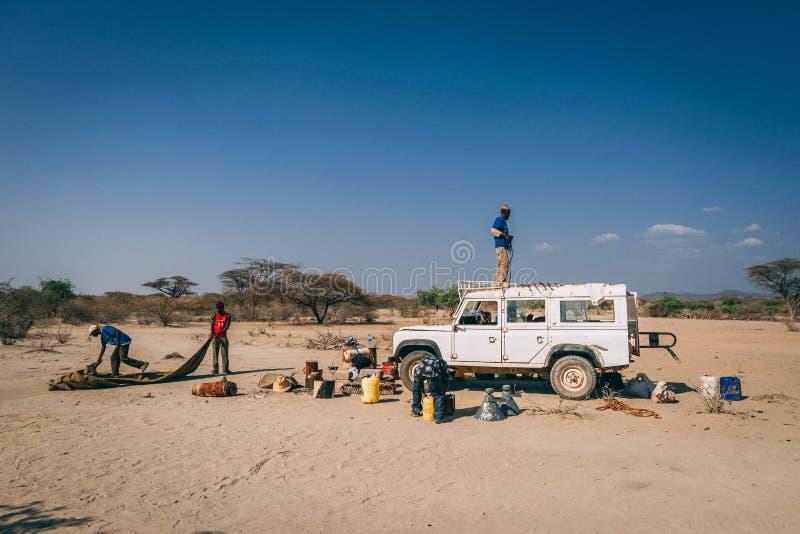 Местные африканцы настраивая лагерь рядом с тележкой стоковое фото rf