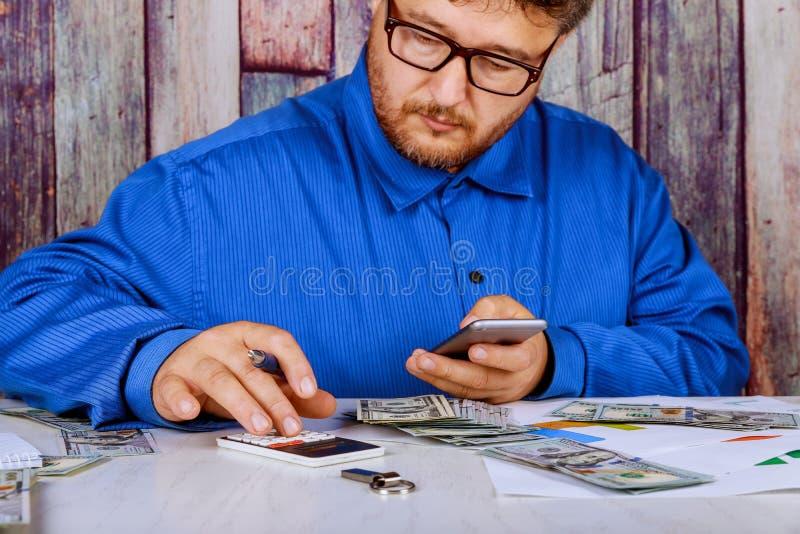 Местный бизнесмен используя калькулятор полной цены оплаченный счетами доллара США стоковая фотография