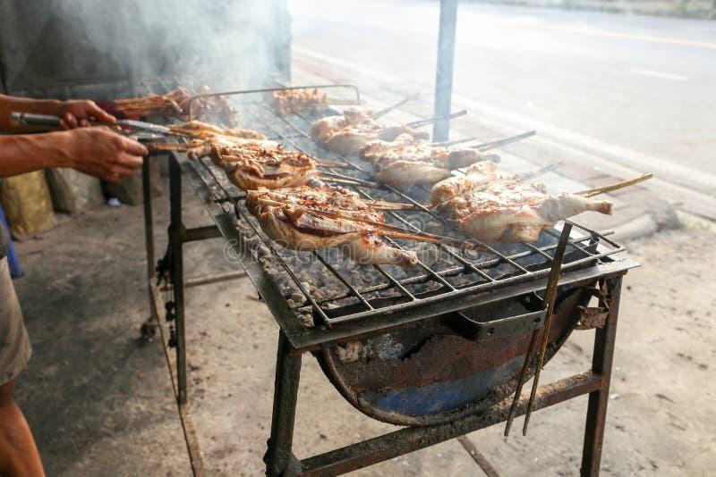 Местный продавец делает тайским цыпленк цыпленка зажаренный в духовке стилем, еду улицы Таиланда стоковые фото
