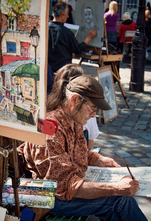 Местный художник на работе на месте du Tertre Парижа Montmartre стоковая фотография