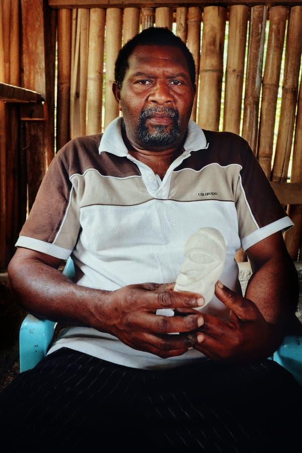 местный человек от деревни держа высекаенный племенной волшебный камень на его тропическом бамбуковом доме стоковая фотография