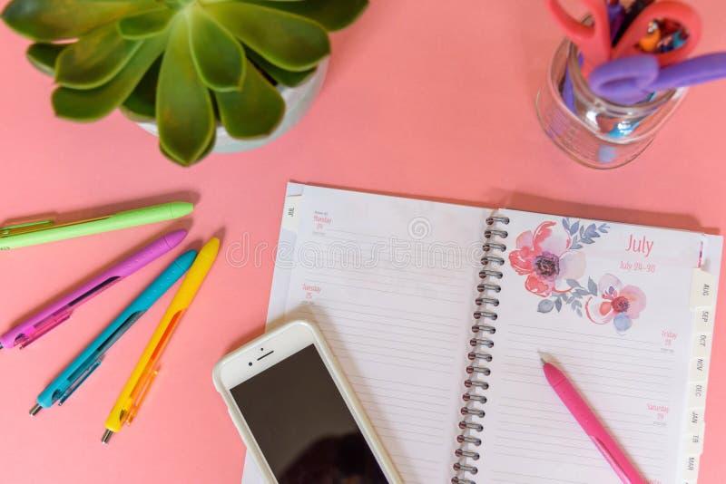 Место для работы взгляд сверху домашнее с открытым календарем на розовой предпосылке стоковое изображение rf